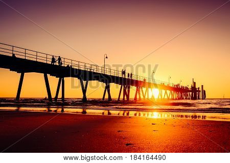 People walking on Glenelg beach jetty at sunset Adelaide South Australia