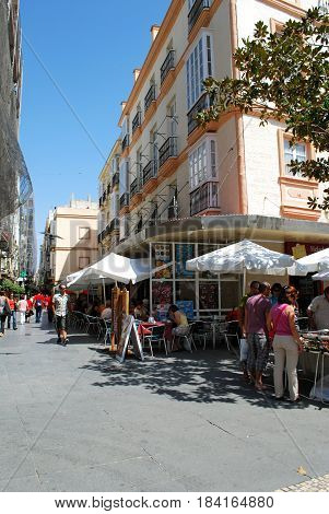 CADIZ, SPAIN - SEPTEMBER 8, 2008 - Tourists relaxing at pavement cafes on corner of Plaza de las Flores and Colunela Cadiz Cadiz Province Andalusia Spain Western Europe, September 8, 2008.