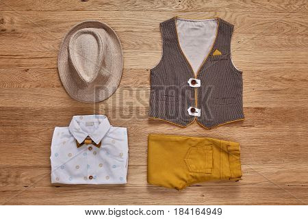 Top view of the kids fashion clothes with accessories on the wooden background. White shirt with print, brown vest, bowtie, brown pants and hat. Elegant clothes for little boys. Concept of the children's fashion.
