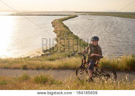 Happy boy riding his mountain bike at sunset, enjoying the nature, beautiful trail winding ahead through the bay.
