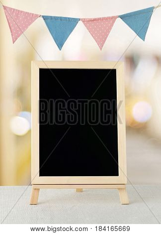 Blank chalkboard standing over colorful party flags and blur background with copy space for text new year and festival card banner