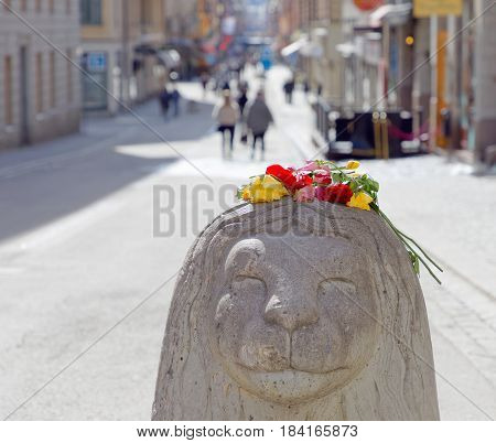 STOCKHOLM SWEDEN - APR 17 2017: Withered flowers on concrete lion on Drottninggatan in central Stockholm from people paying respect to the victims in the terror attack in Stockholm April 07 2017. April 17 2017 in Stockholm Sweden