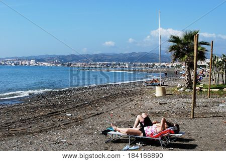 LAGOS, SPAIN - OCTOBER 27, 2008 - Tourists relaxing on the pebble beach with views along the coastline Lagos Malaga Province Andalusia Spain Western Europe, October 27, 2008.