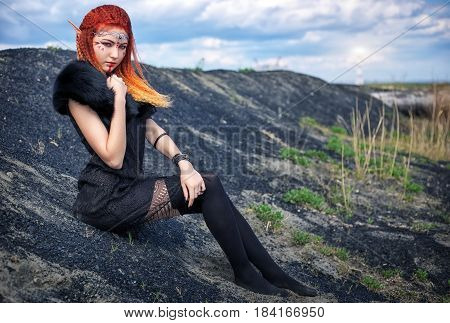 Elf women with fiery hair on nature. Beautiful young fantasy girl. Cosplay character