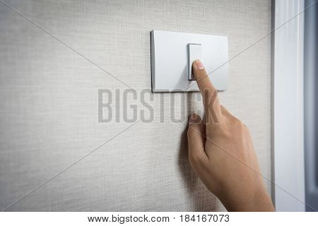Close up hand turning on or off on grey light switch with texture background. Copy space.