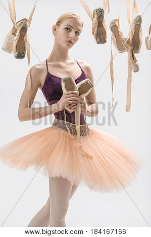 Pretty ballerina in a violet top and a peach tutu stands on the light background in the studio. Around her there are several hanging beige pointe shoes. She holds one pair in the hands. Vertical.