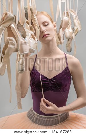 Sensual ballerina with closed eyes in a violet top and a peach tutu stands between hanging beige pointe shoes on the gray background in the studio. She holds a ribbon of the ballet shoe. Closeup.