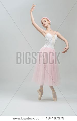 Young ballerina stands on pointes on the gray background in the studio. She wears a dance wear with white top and a rose skirt and has a wreath on her head. Her right hand is in the air. Vertical.