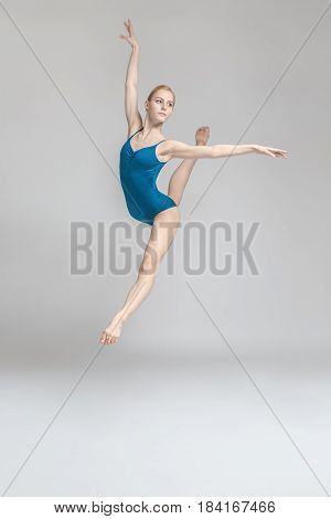 Wonderful ballerina posing in the jump on the gray background in the studio. She wears a blue leotard and looks to the side. Her legs and arms stretched to the sides. Vertical.