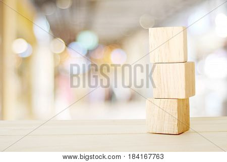 Three wooden cubes on table over blur abtract bokeh light background