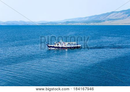 A steel motor boat on Lake Baikal on a summer morning. View from Cape Hadarta to the southwest. Small Sea Strait