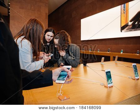 STRASBOURG FRANCE - APR 27 2016: Group of teenager friends girls testing playing on the lastest iPhone smartphone in Apple Store. Apple iPhone tends to become one of the most popular smart phones in the world in 2016