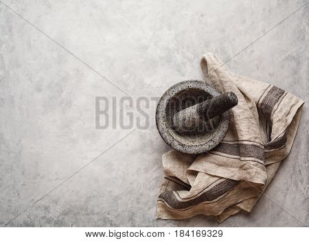 Empty granite mortar and kitchen towel on a gray textured background with copy pace for your text