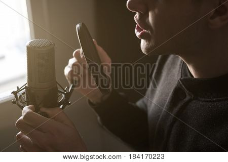 A Close-up Of Lips At The Microphone Of A Singing Young Man Standing In Profile In The Rays Of The S