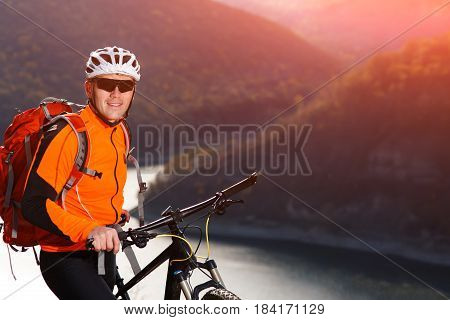 Close-up view photo of mountain cyclist while stands under the river against beautiful landscape. Sportsman in the orange jacket, sunglasses, helmet and with red backpack. Spring season in the countryside. Healthy lifestyle.