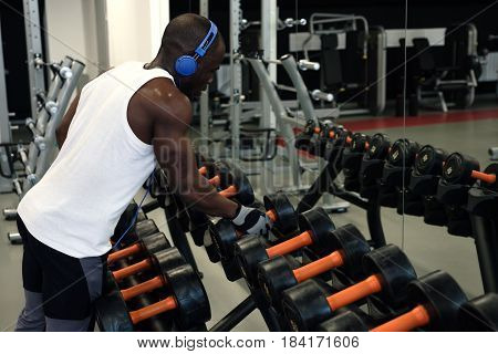 Muscular Black Man In A White T-shirt Doing Exercises With Dumbbells In Front Of The Mirror
