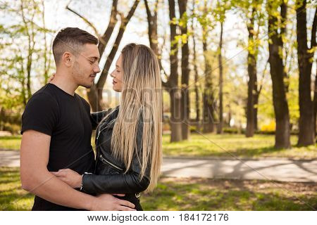 Blonde girlfriend and her boyfriend in the park. In love and relationship. Happines and love