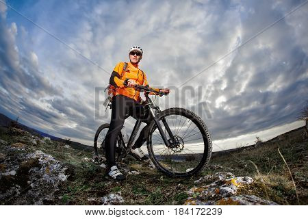 Portrait of the young cyclist standing with bike on the rocks against dramatic sky with clouds. Sportsman in the orange jacket, helmet, sunglasses and with red backpack. Fisheye. Beautiful landscape. Spring season in the countryside.