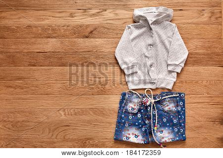 Children's clothing on wooden background. White jacket with hood and blue jeans in flowers. Concept of the children's fashion. Clothes for girls.
