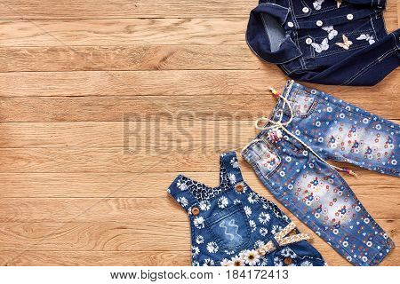 Children's jeans, jacket and denim dress on wooden background. Blue denim jacket, blue jeans in flowers and denim dress in flowers with cute belt. Clothes for little girl. Casual and modern chidren's style.