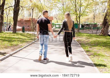 Boyfriend and girlfriend taking a walk in the park. In love and relationship. Happines and love