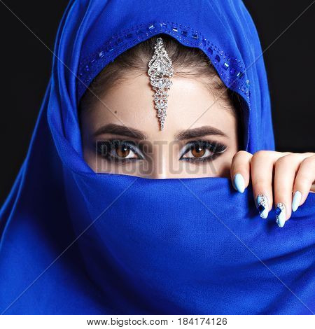Gorgeous Young East Woman face portrait in hijab. Beauty Model Girl with bright eyebrows, perfect make-up, touching her face. Traditional. Isolated on black background. Smokey.Jewelry on her face. Studio