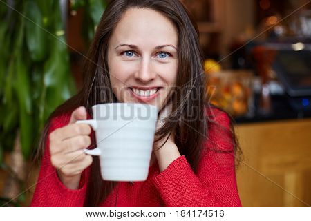 Young natural cheerful Caucasian brunette blue-eyed girl in red sweater is having her breakfast in modern organic coffee shop. Looking and smiling happily at the camera. Youth and beauty concept.
