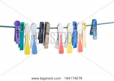 Several different spring-type new and old varicolored plastic clothespins and one old wooden clothespin hanging on the clothes line on a light background