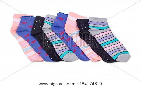 Several different varicolored women's socks laid out in a row on a light background