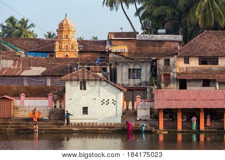 Gokarna, India - January 22, 2016: Unidentified indian people bathing in the sacred lake in Gokarna. The city is a holy pilgrimage site for Hinduists