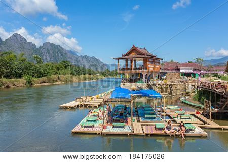 Vang Vieng, Laos - January 19, 2017: Unidentified tourists rest in riverfront restaurant in Vang Vieng, Laos