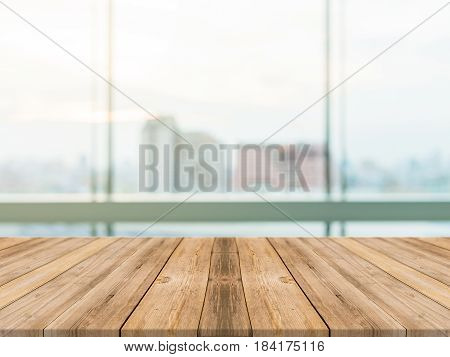 Wooden board empty table top blurred background. Perspective brown wood table over blur city building view background - can be used mock up for montage products display or design key visual layout.