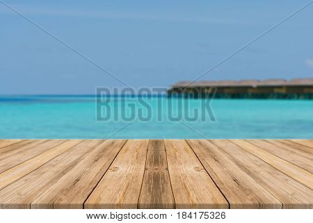 Wooden board empty table top blur sea & sky background. Perspective brown wood table over sea and sky - can be used mock up for montage products display or design key visual layout. summer concepts.