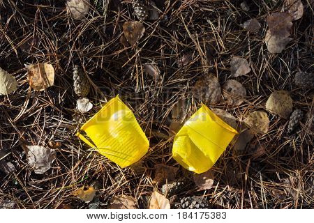 yellow plastic cups on the ground. ecology concept