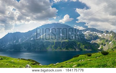 Mountain lake on the background of the craggy mountain with snow patches and sky with clouds and grass meadow on the foreground