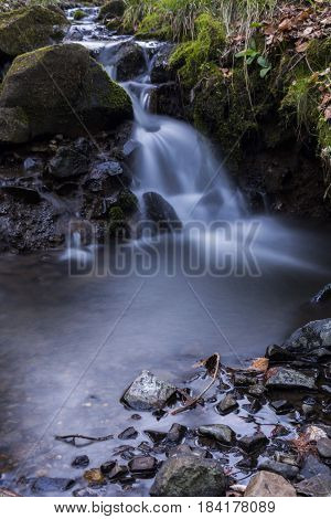 Little waterfall on stream. Water flows between stones with moss and terra with grass. Long exposure.