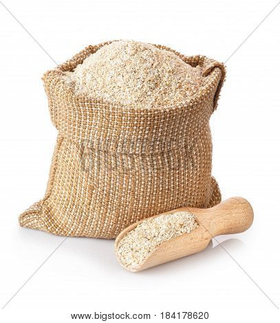 bran in sack and wooden scoop isolated on white background. Food supplement to improve digestion. Dietary fiber. Product for healthy nutrition and diet