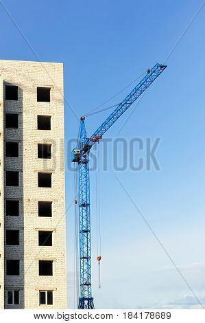 construction site with crane on blue sky background. Small construction project of high-rise housing building. Hoisting crane and unfinished house