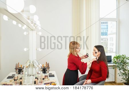 makeup artist doing makeup for young girl.  Make-up artist work with client in studio. Real people. Backstage photo as visagiste apply blush to the cheekbones with big brush