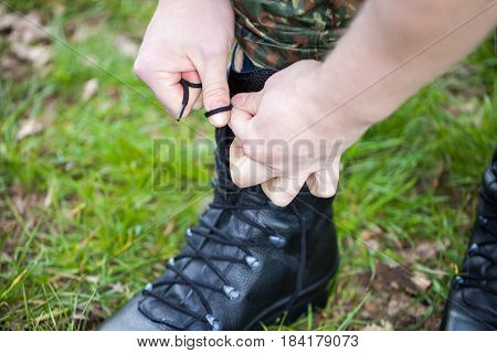 german soldier laces his boots on grass