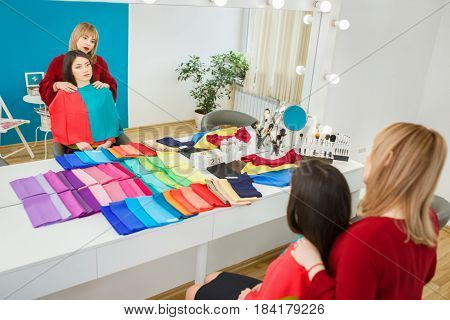 personal color analysis consultation for young woman. Color type test. Image maker determines the colors that best suit an individual based on client natural colorings. Stylist working with girl
