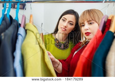 girl with stylist choosing her fashion outfit. Women looking at clothes hanging deciding what to wear. Analysis of wardrobe. Fashion stylist consultation. Master class how to stylishly clothing