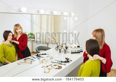 portrait of beautiful happy young woman choosing fashion jewelry. Choice of accessories with stylist