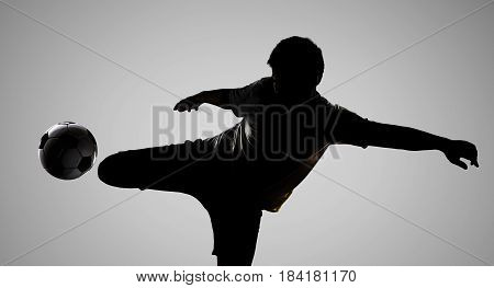 silhouette soccer player kicking the ball on grey background