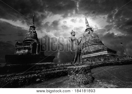 Black and white view of statue of Buddha between great pagoda with beautiful sky within Wat Sa Si at Sukhothai Historical Park Thailand