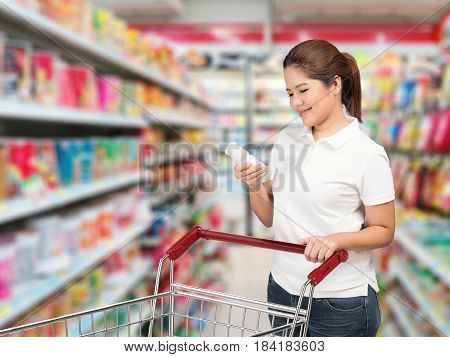 asian woman shopping with shopping cart in supermarket