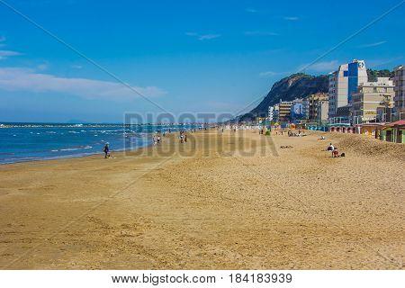 PESARO, ITALY - APRIL 30, 2017: Tourist walking on Pesaro beach in the summer season, Marche, Italy