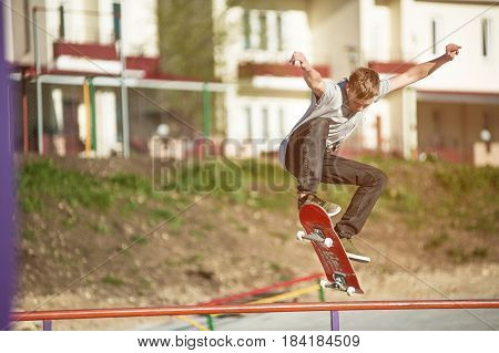 A teenager skateboarder does an ollie trick in a skatepark on the outskirts of the city Against the background of the sleeping area