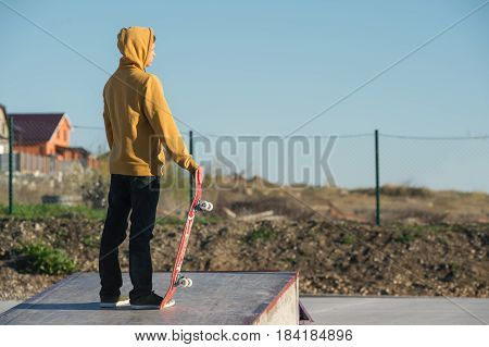 A teenager standing in a yellow hoodie holds a hand skateboard against the backdrop of the outskirts of the city's shantytown and blue sky