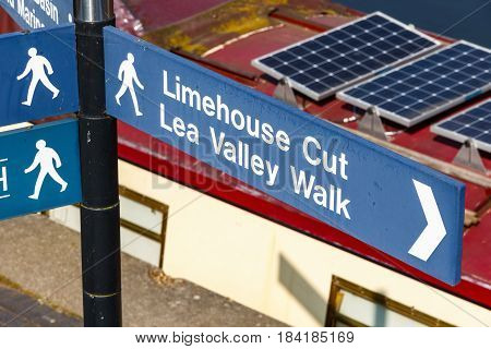 Limehouse Cut and Lea Valley Walk street sign in London with a narrowboat in the backgroun